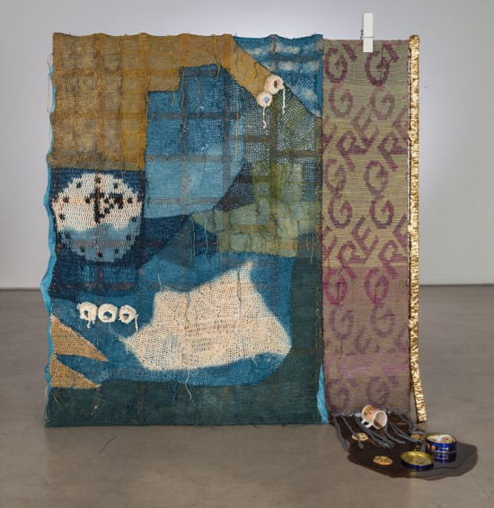 Josh Faught, Greg 2014, Hand woven and crocheted hemp (hand dyed in colors to match the 2013/2014 color forecast, Indigo, gold spray paint, sequin trim, silk, wool, giant clothes pin, spill (resin) with Cathy mug, chocolate chip cookies (plastic), and tin of butter cookies (plastic and metal) on Cedar support